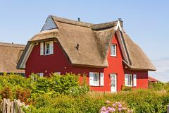 red thatched-roof vacation house - stock photo