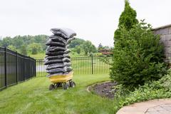 mulch in bags piled high on a cart in the garden - stock photo