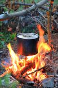 Kettle on tourist camp fire Stock Photos