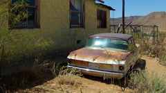 Junk Rusting Car Next To Derelict House In Desert - stock footage