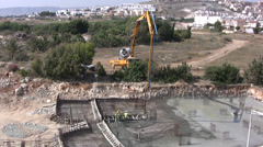 Construction workers laying concrete foundations on a building site Stock Footage