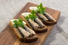 sprats lying on pumpernickel bread - stock photo