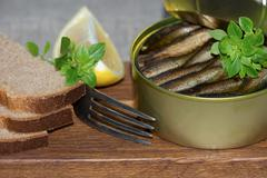 Sprats in a tin and coarse rye bread Stock Photos