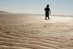 Silhouette of Boy Walking Away on Beach Stock Photos