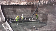 Stock Video Footage of Construction workers piping cement into steel mesh foundations
