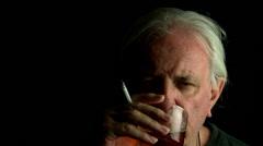 older man drinks while smoking - stock footage