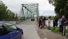 People watching flood river flow,cars passing across steel bridge. Stock Footage