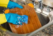 Stock Photo of cleaning wooden cutting board inside of kitchen sink with sponge and soapy wa