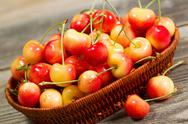 Stock Photo of freshly picked golden rainier cherries in basket on rustic wood