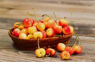 Stock Photo of juicy golden rainier cherries in basket on rustic wood