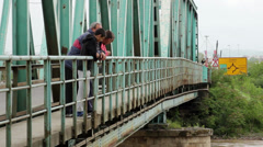 People looking turbulent flood river from the iron bridge,tilt down. Stock Footage