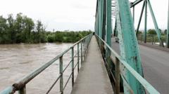 Fast muddy flood river flows under old steel bridge, cars passes. Stock Footage