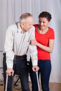 Woman helping a disabled to walk Stock Photos
