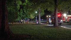 Night scene firefighters and firetrucks wide shot Stock Footage