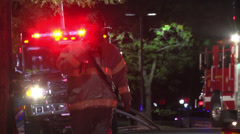 Firefighter on radio walks past firetrucks Stock Footage