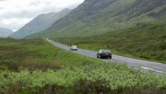 Cars drive along country road in glencoe, scotland Stock Footage