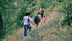 Family, mother and children hike mountain trail for exercise to explore for w Stock Footage