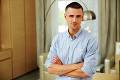 Portrait of a handsome man with arms folded at home Stock Photos