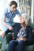 care worker mistreating senior woman - stock photo