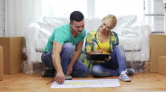 Smiling couple looking at blueprint in new home Stock Footage