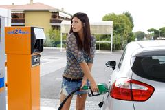 Happy woman pumping gas in car Stock Photos