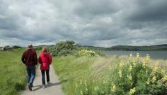 People walk along sand dune path at moray firth, Scotland Stock Footage