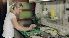 Restaurant kitchen woman preparing fish dishes for guests. Medium shot. Stock Footage