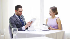 Couple with menus on tablet pc at restaurant Stock Footage