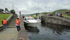 Pan as people pull boat through locks on caledonian canal, scotland Stock Footage