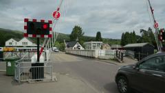 Road swing bridge barrier opens to let cars pass, fort augustus, scotland Stock Footage
