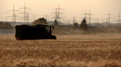 Tractor and combine harvester on a grainfield Stock Footage