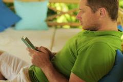 Happy man tweeting on smartphone in the garden, steadycam shot Stock Footage