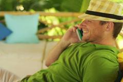 Man talking on cellphone in the garden, steadycam shot Stock Footage