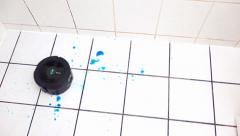 Cleaning robot vacuum cleans the bathroom floor Stock Footage