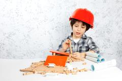 boy plans to build a house - stock photo
