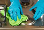 Stock Photo of gloved hands removing soap from stove top range with microfiber rag