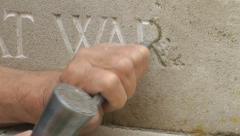 War Memorial - Stone Mason repairs names of soldiers killed in action Stock Footage