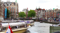 Amsterdam tour boats on dutch canal in middle of city Stock Footage