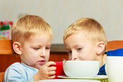 boys kids children eating corn flakes playing with mobile phone - stock photo