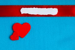 Valentines day background. paper blank hearts on blue fabric material Stock Photos