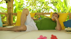 Man drinking juice and resting on bed in the garden Stock Footage