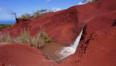 Glidecam of red dirt waterfall Stock Footage