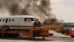 Airport firetruck spraying water towards airplane with fire Stock Footage
