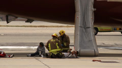 Firemen attending victims at fake plane crash Stock Footage