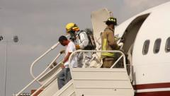 Firemen helping victims off airplane Stock Footage
