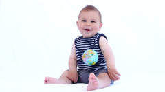 Baby boy playing with globe ball on a white background Stock Footage