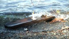 White Funeral Candle Burns Dangerously on Floating Log Rocked by Restless Waves Stock Footage