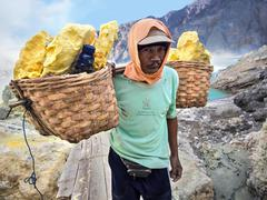 Sulfur Miner at Kawah Ijen Volcano, East Java, Indonesia - stock photo