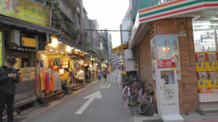 Foreign students walk in shida lane outside 7-11 Stock Footage