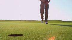 Male Golfer Retrieving Ball From Hole - stock footage